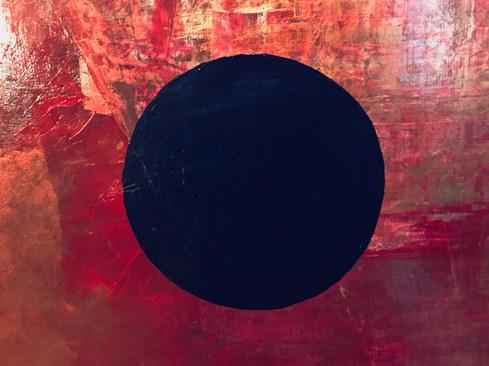 Tief dunkelblauer Kreis auf rot-magenta-goldenem Hintergrund