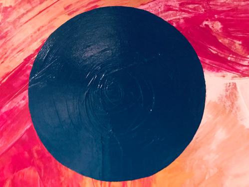 Türkiser Kreis auf rot-weiß-gold-gelbem Hintergrund