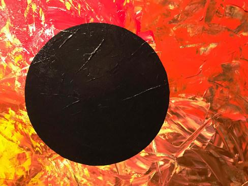 Tiefschwarzer Kreis auf rot-gelb-orange-kupfer Hintergrund mit schwarzem Rand