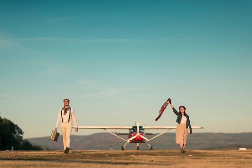 Stylish couple walking on airfield with