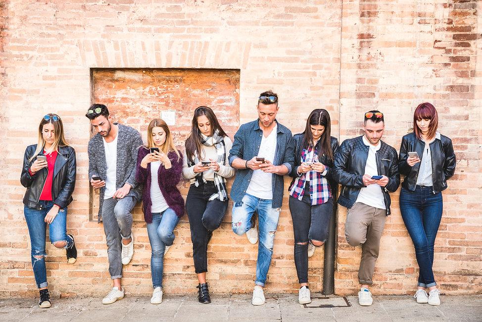 Gruppe von Freunden lehnt mit dem Smartphone in der Hand an der Mauer