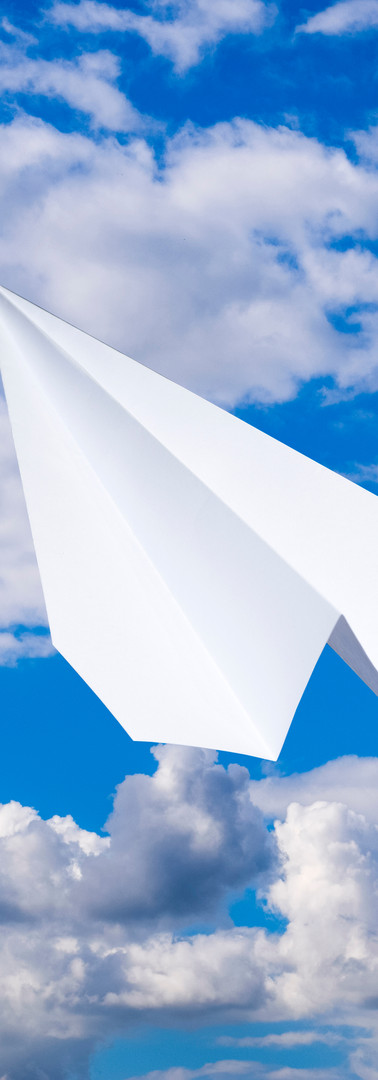 White paper airplane in a blue sky with