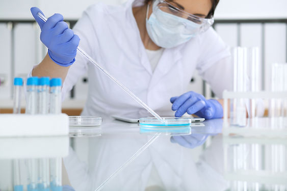 Female lab technician performing science with pipette