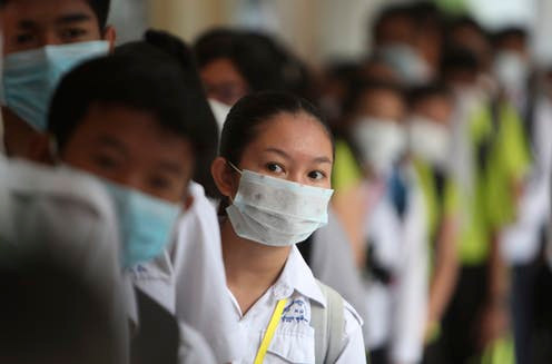 Students line up to sanitize their hands to avoid the contact of coronavirus in Phnom Penh, Cambodia, Jan. 28, 2020. AP Photo/Heng Sinith