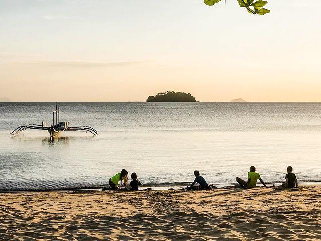 Kids enjoying the beach at sunset.