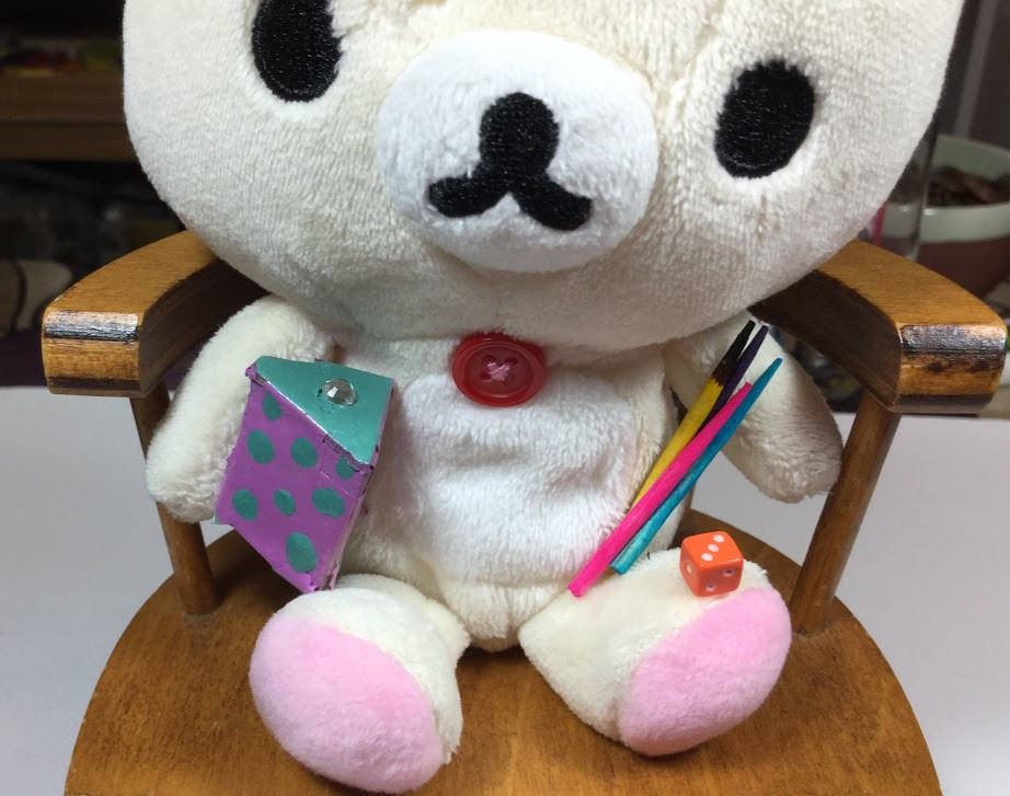The bear is holding colored pencils.
