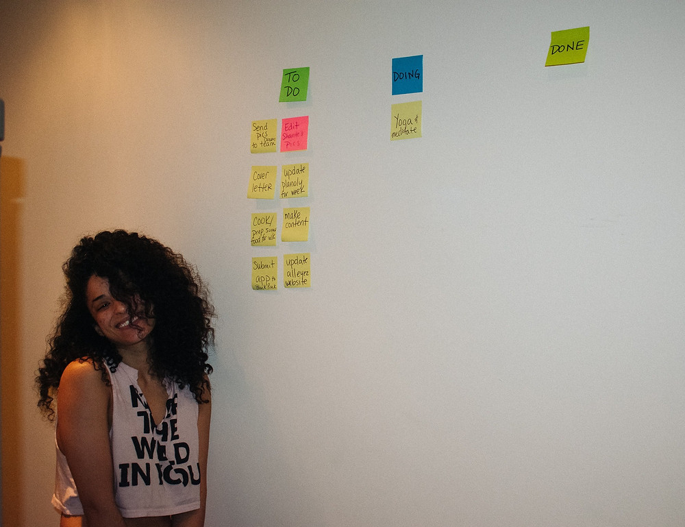 Picture of woman next to a wall of post its that are organized into three columns: To Do, Doing, Done