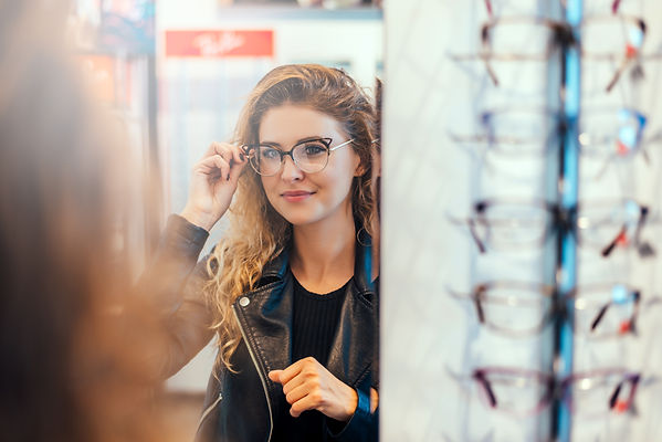 young woman trying on glasses ray ban