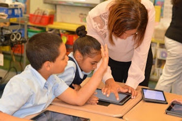 teacher working with two students