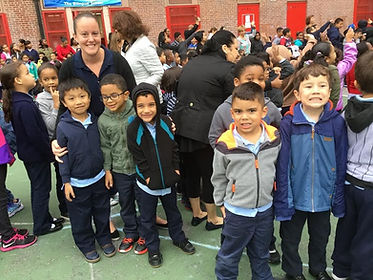 Horizon teacher with students posing for picture outside of the school.