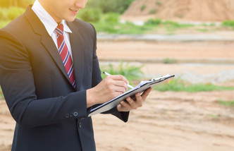 Businessman surveying land for industria