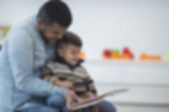 Dad and toddler son reading a book.jpg