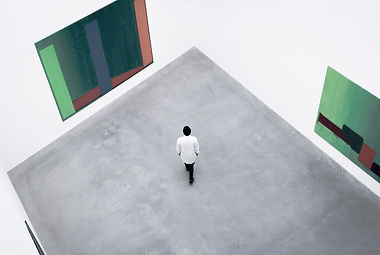 A man in a large art exibition space looking at a painting