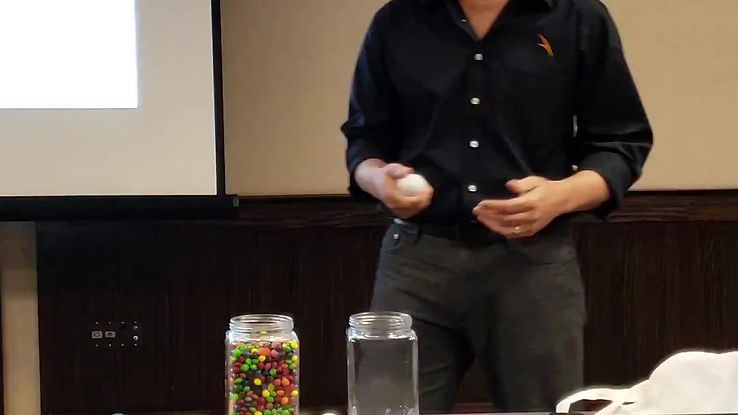 Health Club Doctor, Jarrod Saracco giving a presentation at the 2018 MACMA Conference on effective time management skills nad setting priorities by means of golf balls and jelly beans.