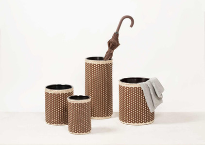 Pigment France bins and umbrella stands featuring bronze inner with woven rattan and leather.