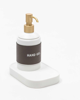 Leather-accented hand sanitiser dispenser with Corian drip tray and brass pump detail