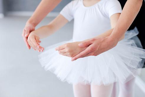 Ballet teacher helps little ballerina in