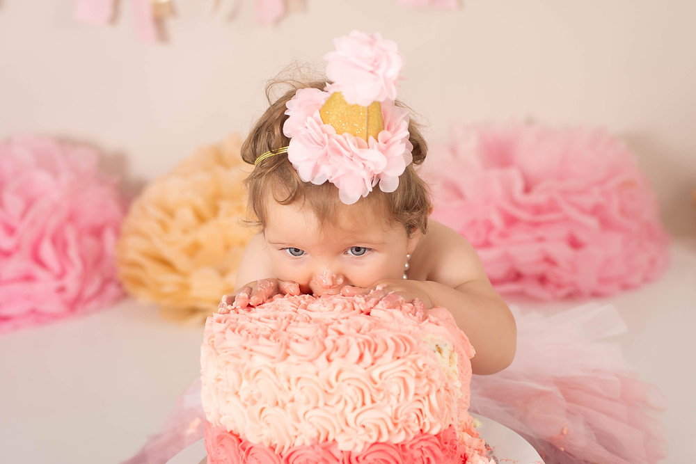 baby girl eats cake at her cake smash photo shoot