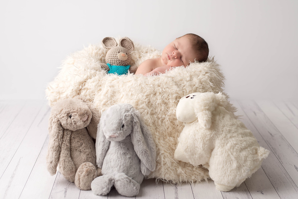 Newborn baby surrounded by toys