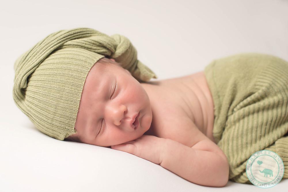 Sleeping newborn in green hat
