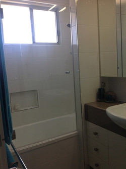Shower over bath with built in shelf