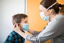 mom puts mask on kid.jfif