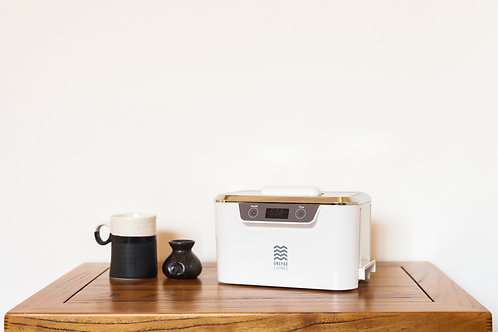 OneLivings Ultrasonic Cleaner S300 White on wooden coffee table with a ceramic mug