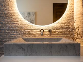 Floating illuminated mirror over powder room marble vessel sink