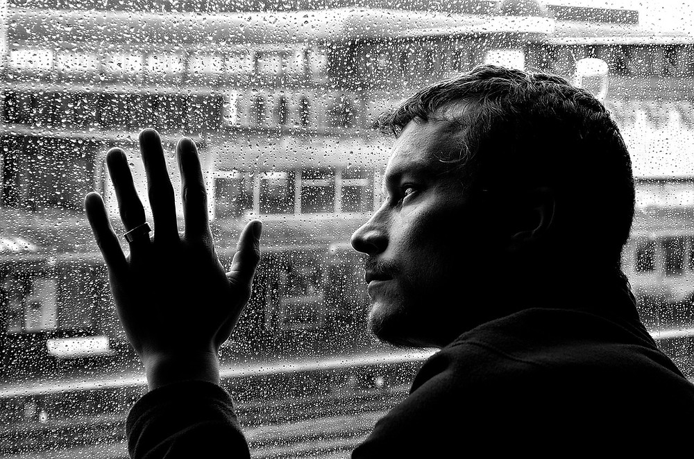 Depreesed man looking outside at a rainy day with his hand and head on the window