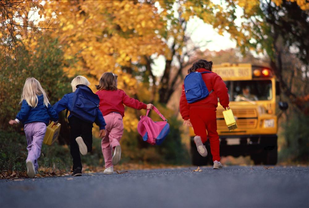 4 kids running after a school bus