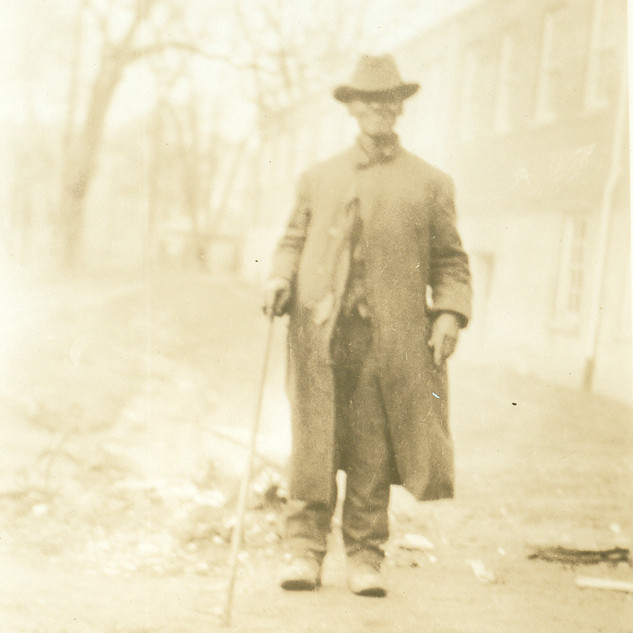 Clem Bolden wearing hat, coat with cane