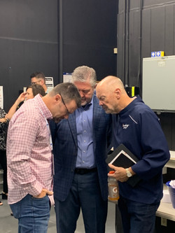 Pastors praying together before one of the sessions