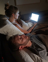Light from woman reading her iPad in bed keeping bed partner awake