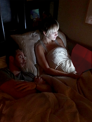 Bed partner sleeps peacefully while woman reads her iPad with her Hoodi on