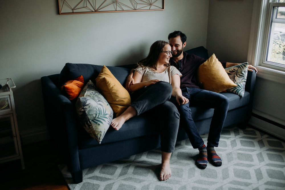 Couple sitting on couch in their home for engagement photos