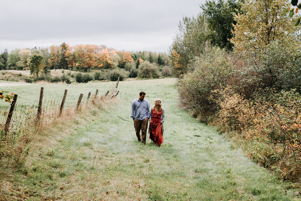 couple walking in a filed during their engagement session