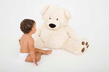 Image of a sitting baby with a huge cuddly bear