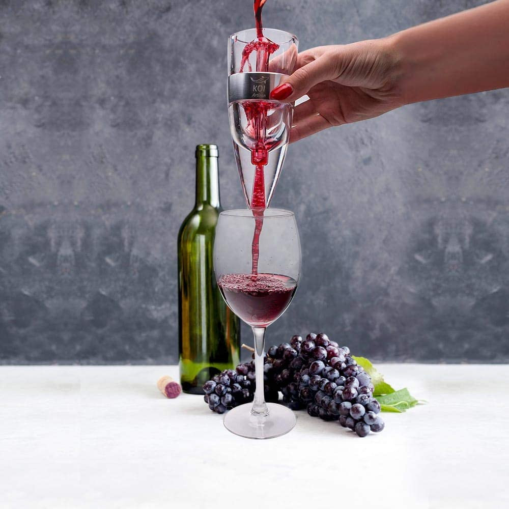 a person pouring red win through an areator into a wine glass