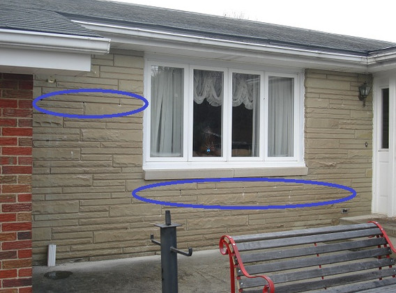 Small holes drilled into mortar joints on a home with stone facade