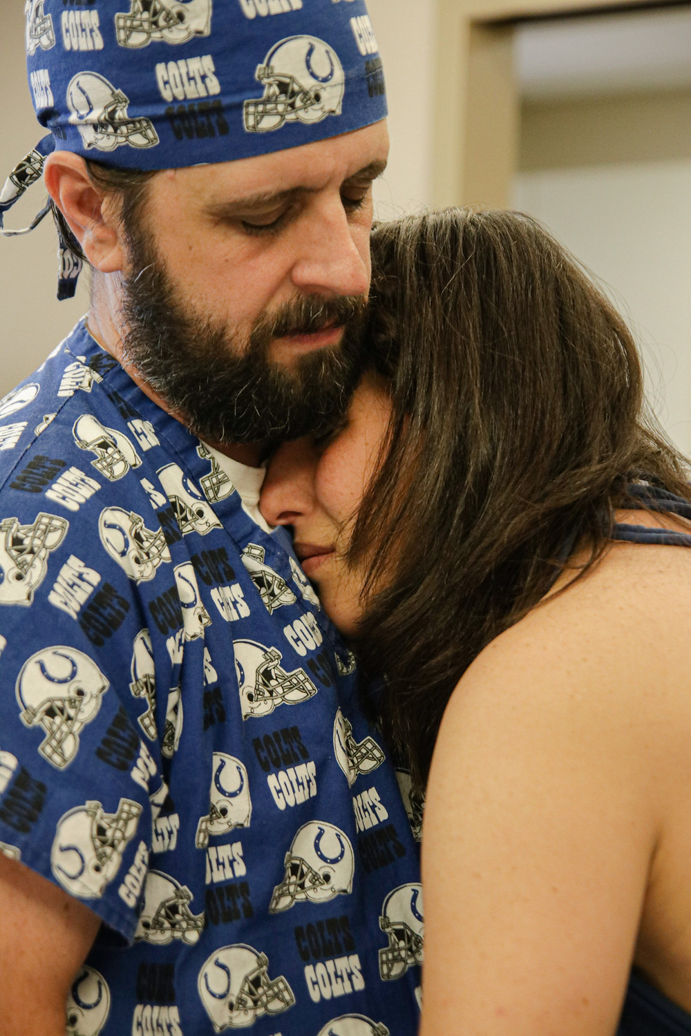 a man in a blue colts dad scrubs holds his wife against his chest as she takes a break from laboring as a supportive birth partner
