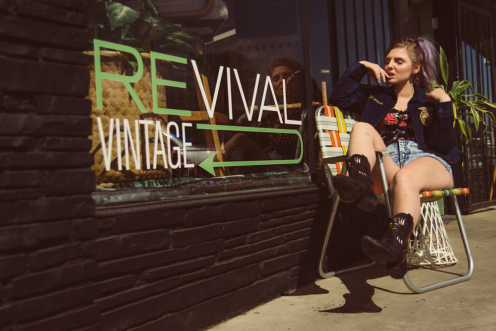 Woman sits with cowboy boots in a vintage lawn chair outside of Revival Vintage