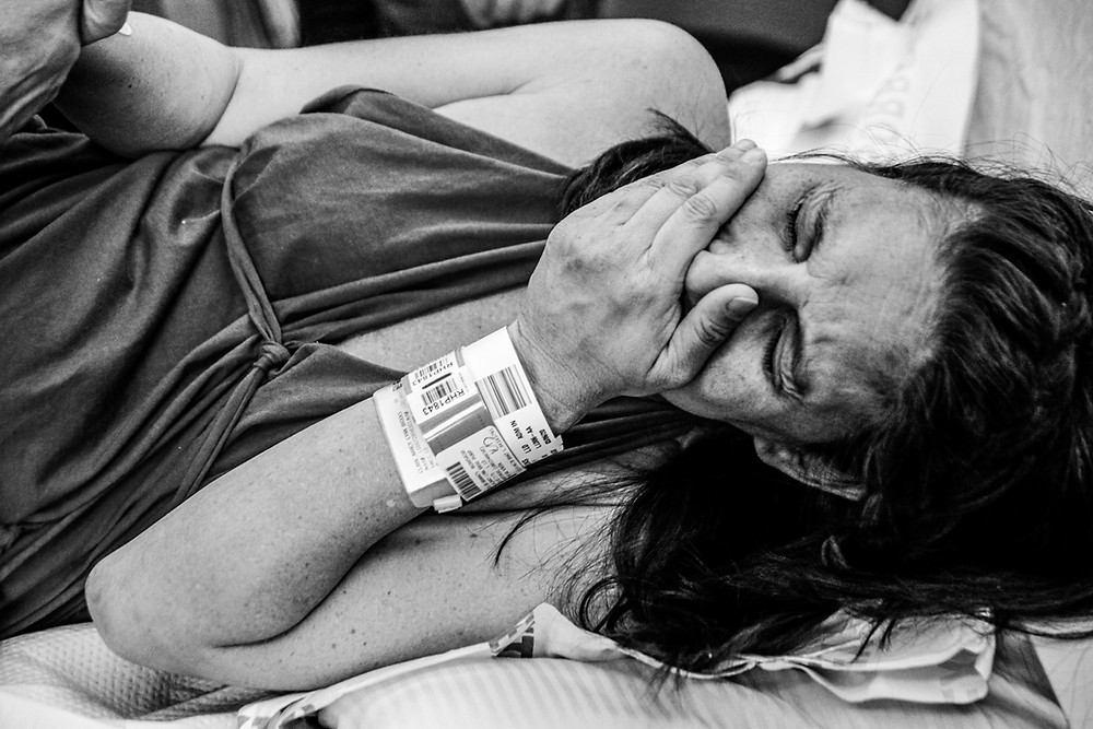 a woman wearing a cotton birthing dress and medical wristbands holds one hand in her husband's hand and the other over her face in pain as she goes through labor