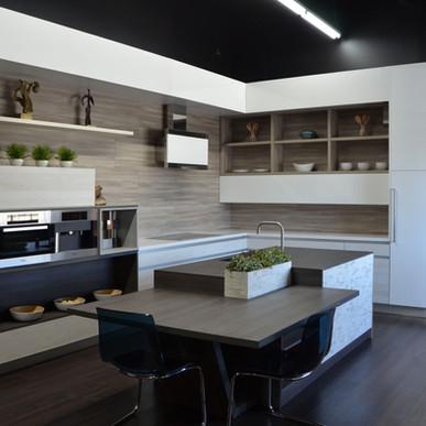High gloss white cabinetry draws focus on Roble backsplash
