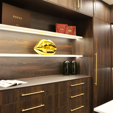 Synchronized matte walnut closet cabinetry with satin gold hardware