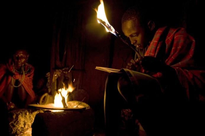 Ο 12χρονος Kelvin Leadismo κάνει την εργασία του κοντά στη φωτιά με τα αδέλφια του στην Kisima της Κένυας