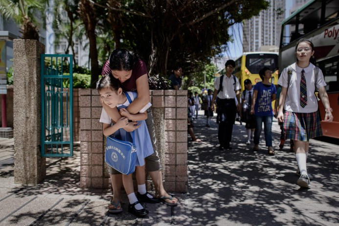 Maia, 5 ετών, δέχεται την αγκαλιά της νταντάς της στο δρόμο για το σχολείο έξω από το σπίτι της στο Χονγκ Κονγκ στις 18 Ιουνίου