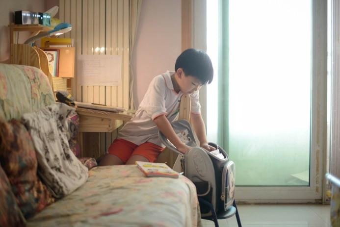 Wei Hanqi, 9, ετοιμάζει την τσάντα του, για να πάει στο σχολείο του στο Πεκίνο στις 19 Ιουνίου