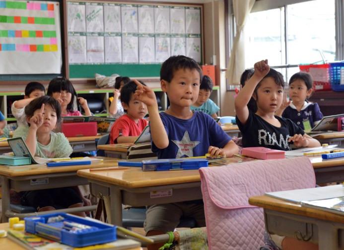 Ο εξάχρονος μαθητής δημοτικού Seishi Nishida σηκώνει το χέρι του, μαζί με τους συμμαθητές στο σχολείο του στο Τόκιο στις 11 Ιουνίου