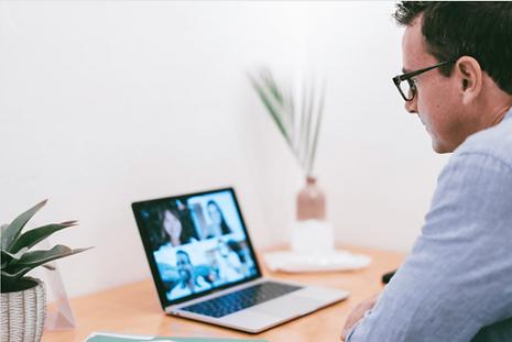 Mann der vor seinem Laptop sitzt und eine Meetin leitet. Er hat gelernt, wie er auch remote eine gute Führungskraft sein kann.
