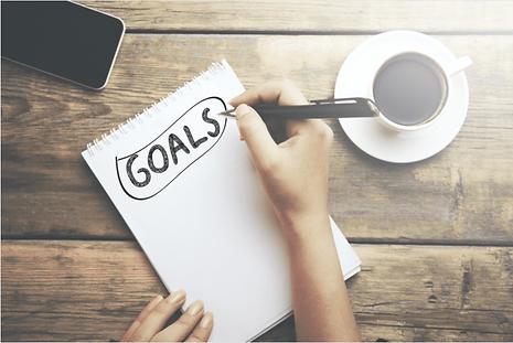 Notizblock auf dem eine Person seine Ziele notiert. Auf dem Tisch liegt noch ein Handy und eine Tasse Kaffee.